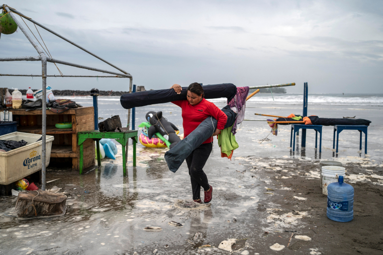 A+woman+removes+umbrellas+from+the+beach+as+strong+waves+reach+the+coast+due+to+Hurricane+Grace%2C+which+has+reached+category+2%2C+in+Boca+del+Rio%2C+Veracruz%2C+Mexico%2C+on+August+20%2C+2021.+-+Grace+regained+hurricane+strength+Friday+as+it+barreled+towards+Mexico+for+a+second+time%2C+triggering+warnings+of+flooding+and+mudslides+in+mountains+on+the+eastern+mainland.+