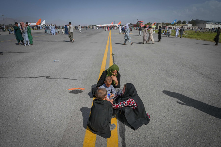 Afghan people sit along the tarmac as they wait to leave the Kabul airport in Kabul on August 16, 2021, after a stunningly swift end to Afghanistans 20-year war, as thousands of people mobbed the citys airport trying to flee the groups feared hardline brand of Islamist rule. (Photo by Wakil Kohsar / AFP) (Photo by WAKIL KOHSAR/AFP via Getty Images)
